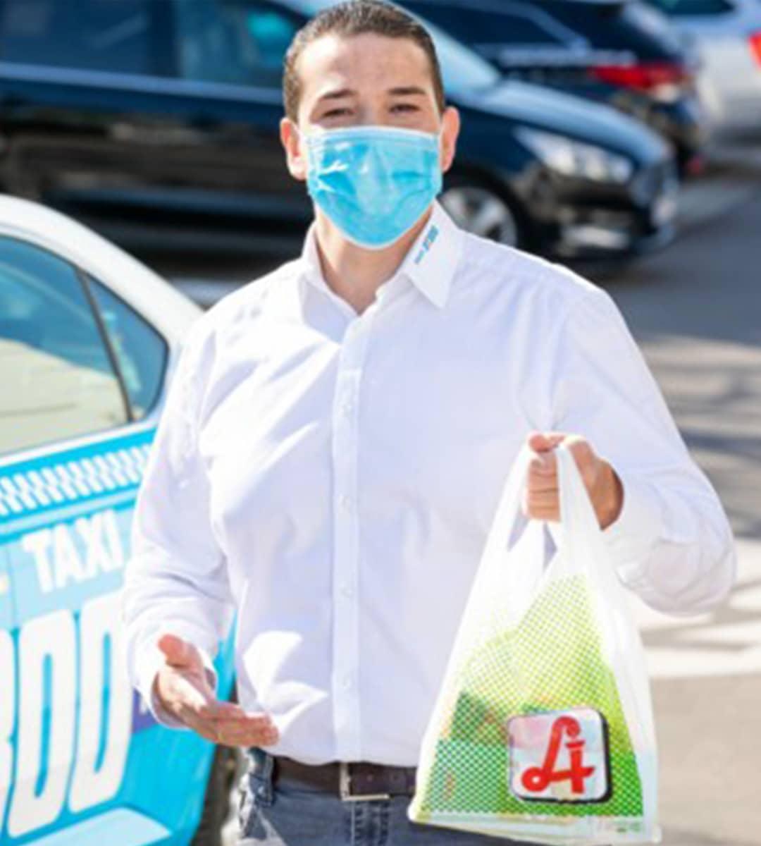 Taxilenker mit MNS-Maske und Einkäufen
