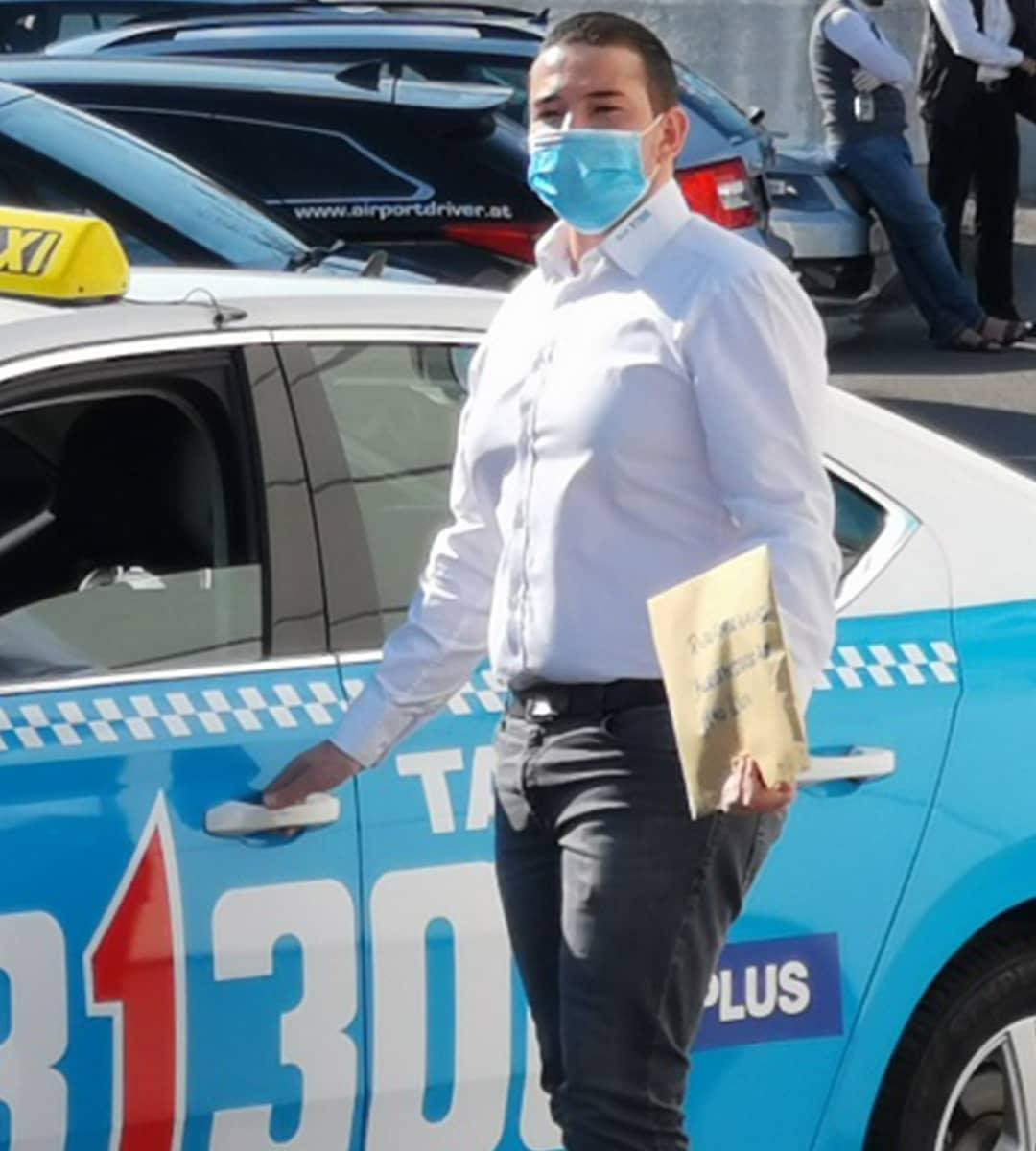 Taxilenker mit MNS-Maske vor Taxi